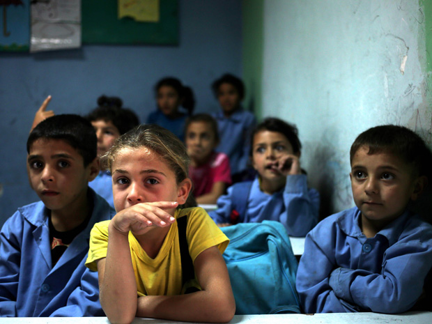 Estudantes sirios acompanham aula em escola para refugiados no Líbano (Foto: Hussein Malla/AP)